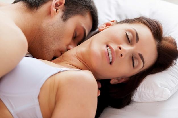 Kocham go całującego mnie! piękna młoda kochająca się para uprawia seks leżąc w łóżku
