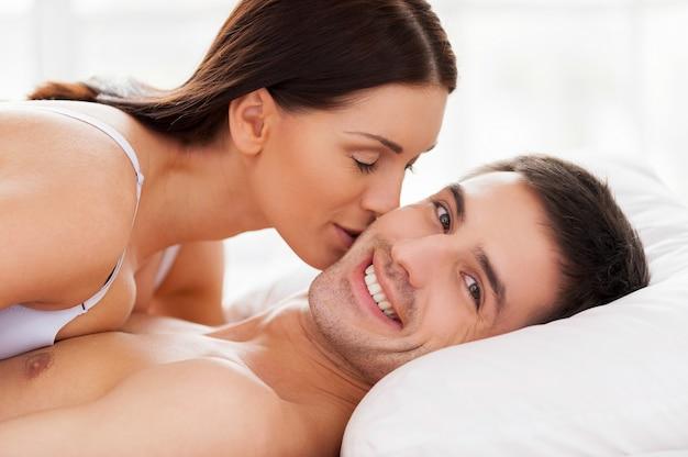 Kocham ją! piękna młoda kochająca para leży w łóżku, podczas gdy kobieta całuje swojego chłopaka w policzek