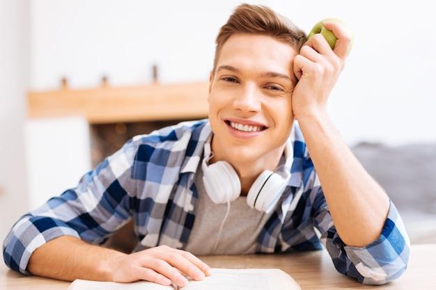 Kocham jabłka. przystojny, czujny jasnowłosy chłopak uśmiecha się i siedzi przy stole z książką i trzyma jabłko