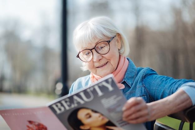 Kocham modę. zainspirowana blond kobieta czyta magazyn siedząc na ławce