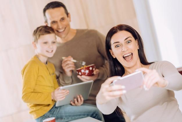 Kocham moich chłopców. optymistyczna młoda kobieta robi sobie autoportret z mężem i synem, jedząc śniadanie i oglądając coś na tablecie