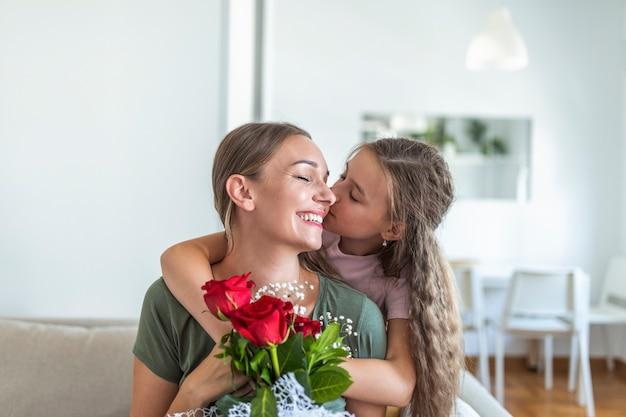 Kocham moją mamę! atrakcyjna młoda kobieta z małą słodką dziewczynką spędzają razem czas w domu, dziękując za ręcznie wykonaną kartkę z symbolem miłości i kwiatami. szczęśliwa koncepcja rodziny. dzień matki.