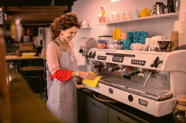 Kocham moją pracę. miła kobieta pochyla głowę podczas przygotowywania kawy