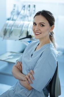 Kocham moje miejsce pracy. dość młoda dentystka pozuje przed aparatem dentystycznym w swoim gabinecie i składa ręce na piersi, uśmiechając się szeroko