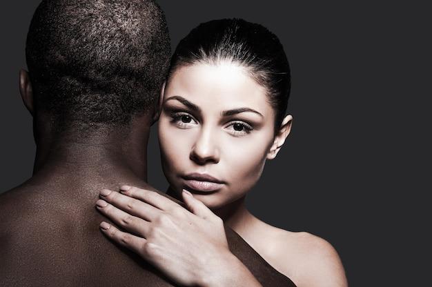 Kocham mojego mężczyznę. piękna kaukaska kobieta przytula czarnego mężczyznę i patrzy na kamerę, stojąc na szarym tle