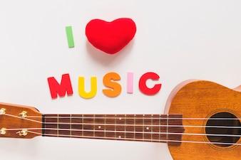 Kocham muzyka kolorowy tekst z drewnianą gitarą na białym tle