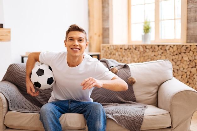Kocham piłkę nożną. dobrze wyglądająca, wesoła, dobrze zbudowana nastolatka, siedząca na kanapie, uśmiechnięta i trzymająca piłkę nożną