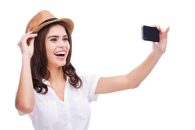 Kocham selfie! wesoła młoda kobieta w modnym kapeluszu robi selfie swoim smartfonem i uśmiecha się stojąc na białym tle