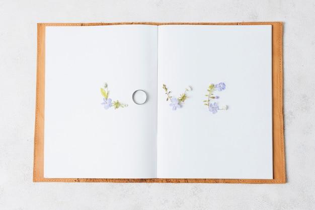 Kocham tekst kwiatowy na otwartej książki na białym tle