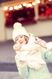 Kocham to. ładna dziewczyna odwiedza jarmark bożonarodzeniowy i zamierza zjeść słodycze