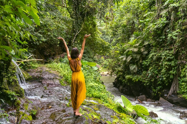 Kocham to. młoda kobieta podczas spaceru po lesie podnosząca obie ręce podczas głębokiego oddychania