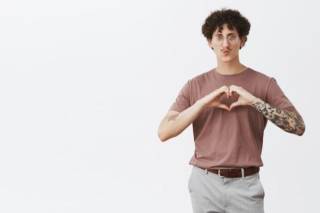 Kocham twój styl. modny przystojny facet z kręconymi włosami z eleganckim wąsem i fajnymi tatuażami na ramionach złożone usta w pocałunku pokazujący gest serca na piersi