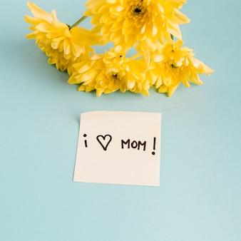 Kocham tytuł mamy na papierze z bukietem kwiatów