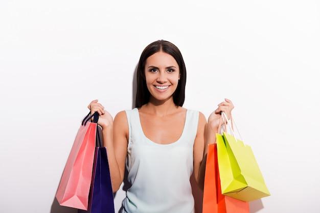 Kocham zakupy! atrakcyjna młoda kobieta w sukience nosząca kolorowe torby na zakupy i uśmiechnięta stojąc na białym tle
