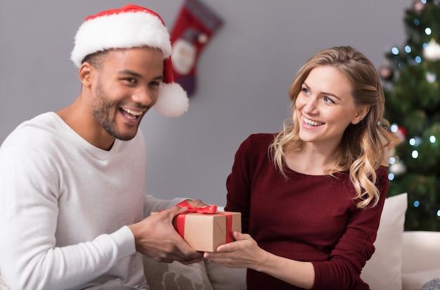 Kochamy boże narodzenie. zachwycona radosna atrakcyjna trzyma pudełko prezentowe i wręczając je swojemu chłopakowi podczas świętowania bożego narodzenia