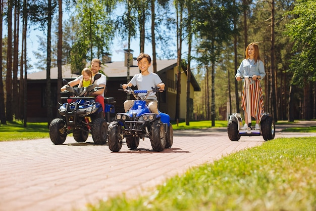 Kochamy jeździć. radosne, urocze dzieciaki spędzające czas z rodzicami i jeżdżące quadami