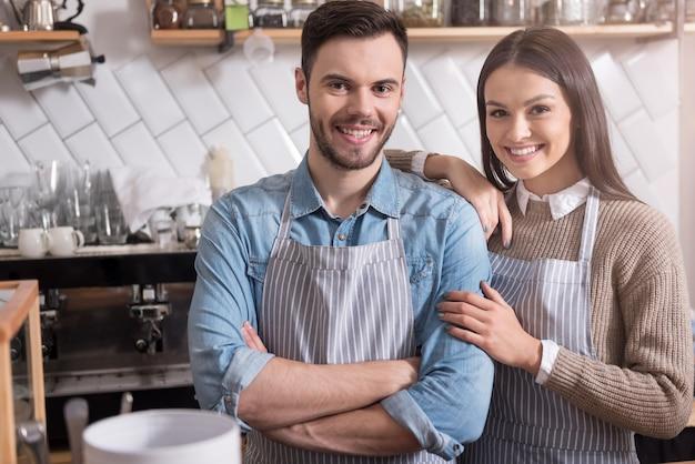 Kochamy naszą pracę. rozbawieni młodzi kelnerzy, stojąc za barem, uśmiechają się i przytulają.