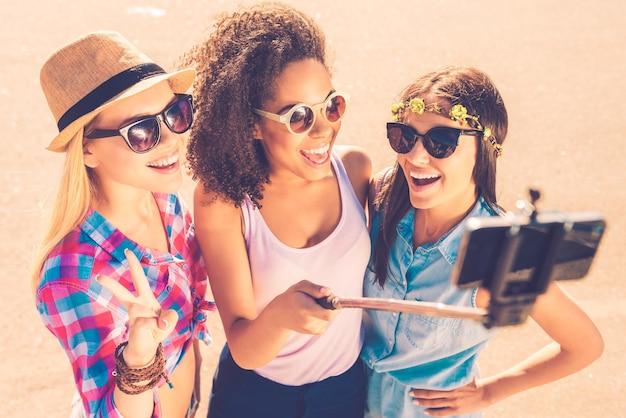 Kochamy selfie! widok z góry na trzy młode, szczęśliwe kobiety robiące selfie za pomocą smartfona, stojąc razem na zewnątrz