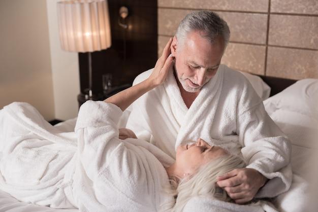 Kochamy. wesoła, rozbawiona para w wieku leżąca na łóżku i dotykająca się nawzajem, wyrażająca miłość i troskę