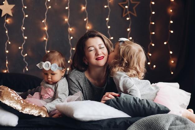 Kochana młoda matka jest całowana przez swoją uroczą córeczkę leżącą na łóżku obok dziecka