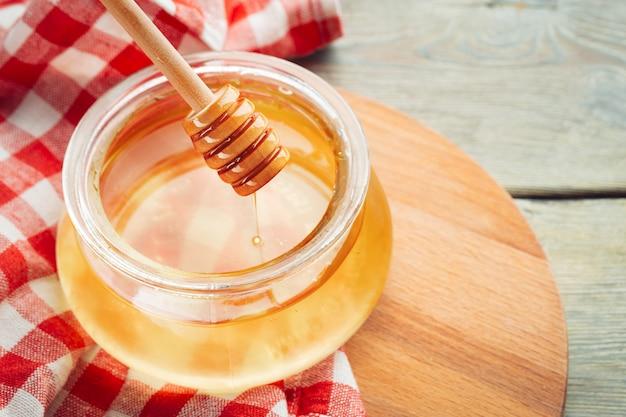 Kochanie . słodki miód w szklanym słoju na drewnianym.