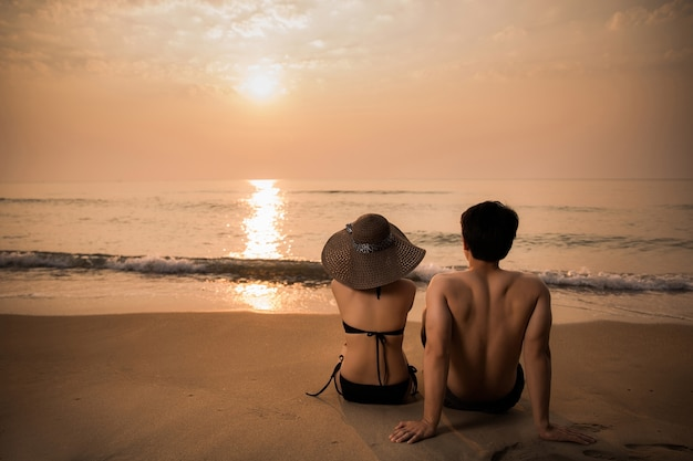 Kochankowie oglądając zachód słońca na plaży.