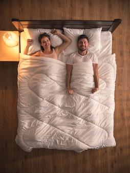 Kochankowie uśmiechu leżeli na łóżku. widok z góry