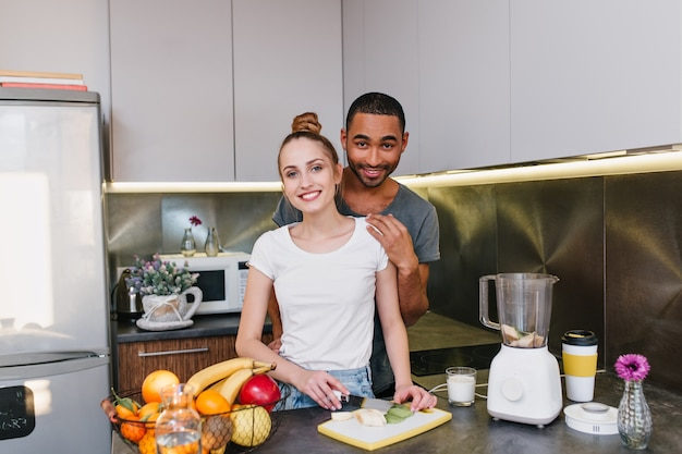 Kochankowie wspólnie gotują w kuchni. dziewczyna z jasnymi włosami tnie owoce. para w koszulkach o radosnych twarzach spędza razem czas w domu.