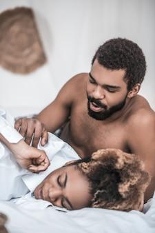 Kochany. uważny, delikatny afroamerykanin budzi się śpiąca żona dotykając ręką rano w łóżku