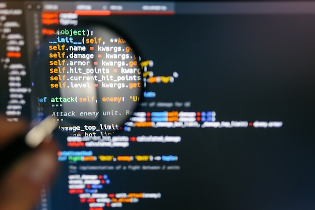 Kod programu na ekranie komputera w lupie. zbliżenie
