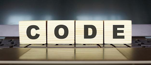 Kod słowa. drewniane kostki z literami na białym tle na klawiaturze laptopa