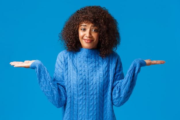 Kogo to obchodzi, nie wiem. zmieszana i nieświadoma głupia śliczna uśmiechnięta afroamerykańska kobieta w zimowym swetrze, wzruszająca ramionami z rękami rozłożonymi na boki i uśmiechająca się, jak nie mam pojęcia, stoi na niebiesko