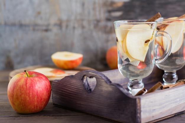Kojąca jabłko i cynamonowa herbata w szkłach na drewnianym stole. detox, lek przeciwdepresyjny. styl rustykalny