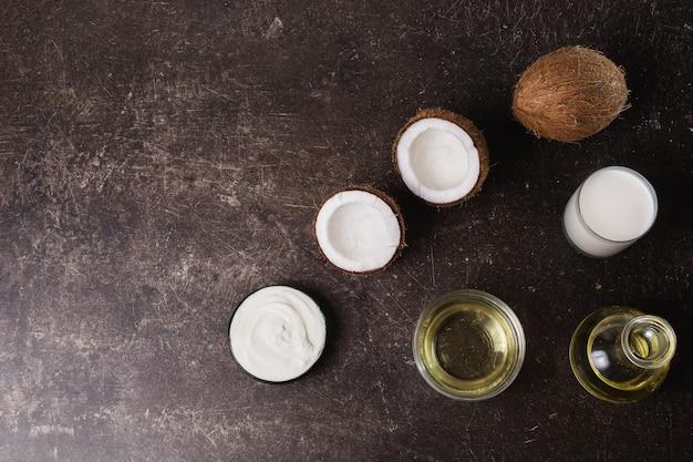 Kokos i olej kokosowy na ciemnym tle marmuru. egzotyczny duży orzech. higieny osobistej. kuracja spa