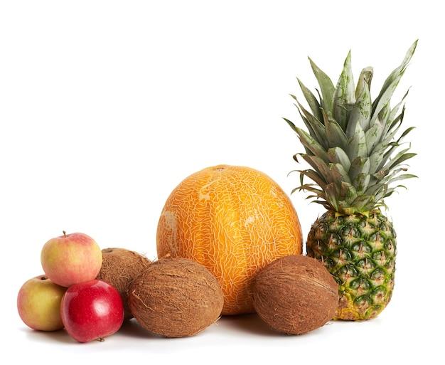 Kokos, melon, jabłko i świeży cały ananas na białym tle na białym tle, zdrowe owoce, z bliska