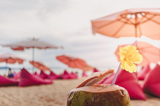 Kokos ozdobiony kwiatem w kawiarni na plaży latem
