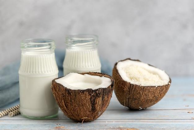 Kokos, słoik mleka kokosowego i płatki kokosowe na jasnym drewnie.