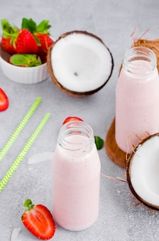 Kokos truskawkowo-kokosowy na mleku kokosowym w szklanym słoiku ze słomką na szarej ścianie. koncepcja zdrowej żywności. orientacja pionowa.