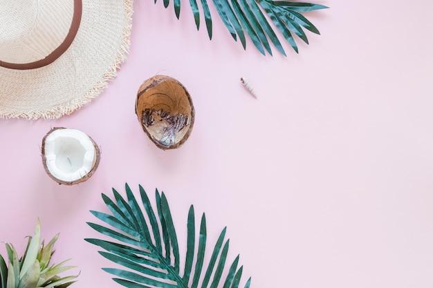 Kokos z liśćmi palmowymi i słomkowym kapeluszem