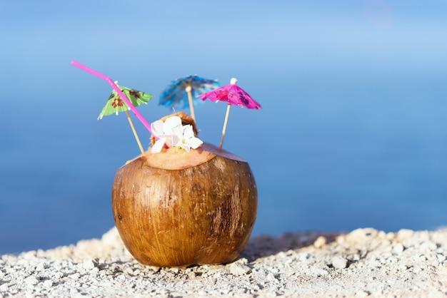 Kokos z słomką do picia, parasole i kwiaty, na skałach na morzu w protaras, cyprus wyspy