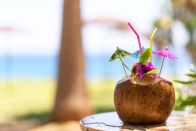 Kokos z słomką do picia, parasole i kwiaty, w pobliżu palmy nad morzem
