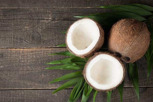 Kokos z zielonymi liśćmi na drewnianym tle.