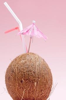 Kokos ze słomką do picia i parasolem na różowym tle z miejsca na kopię.