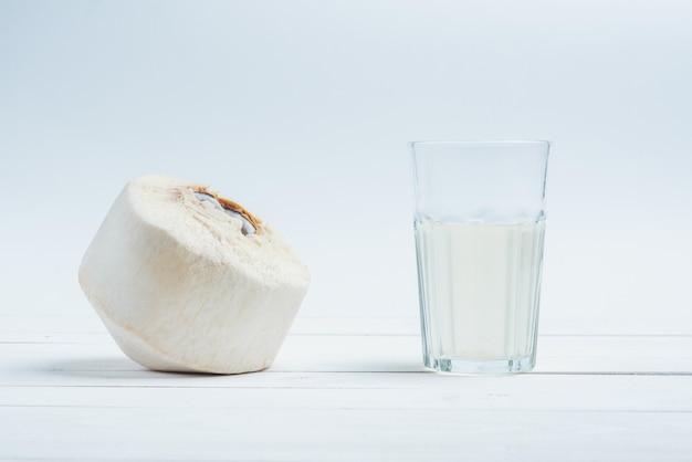Kokos ze szklanką świeżej wody kokosowej