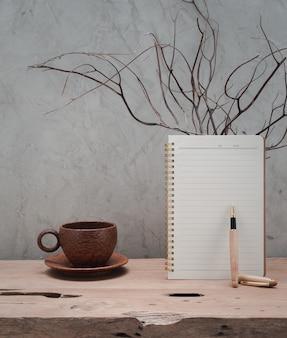 Kokosowa filiżanka do kawy, brązowy notatnik i koral w drewnianym wazonie na drewnianym stole z drewna tekowego