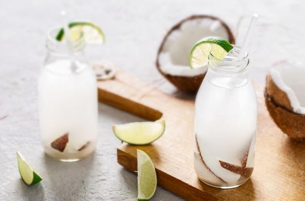 Kokosowa woda w butelkach na drewnianym stole. koncepcja zdrowych napojów