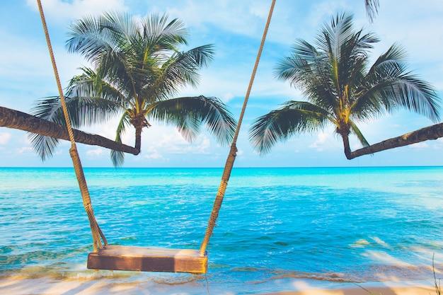 Kokosowe drzewa przylegają do morza z drewnianymi huśtawkami