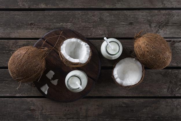 Kokosowe mleko w butelkach na drewnianym stole. koncepcja zdrowego odżywiania