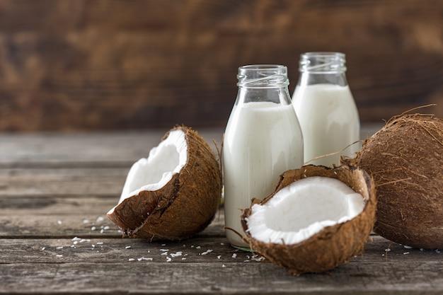 Kokosowe mleko w butelkach na drewnianym stole. wegański napój bezmleczny. koncepcja zdrowego odżywiania
