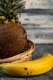 Kokosowy ananas i banan w łozinowym koszu na stole